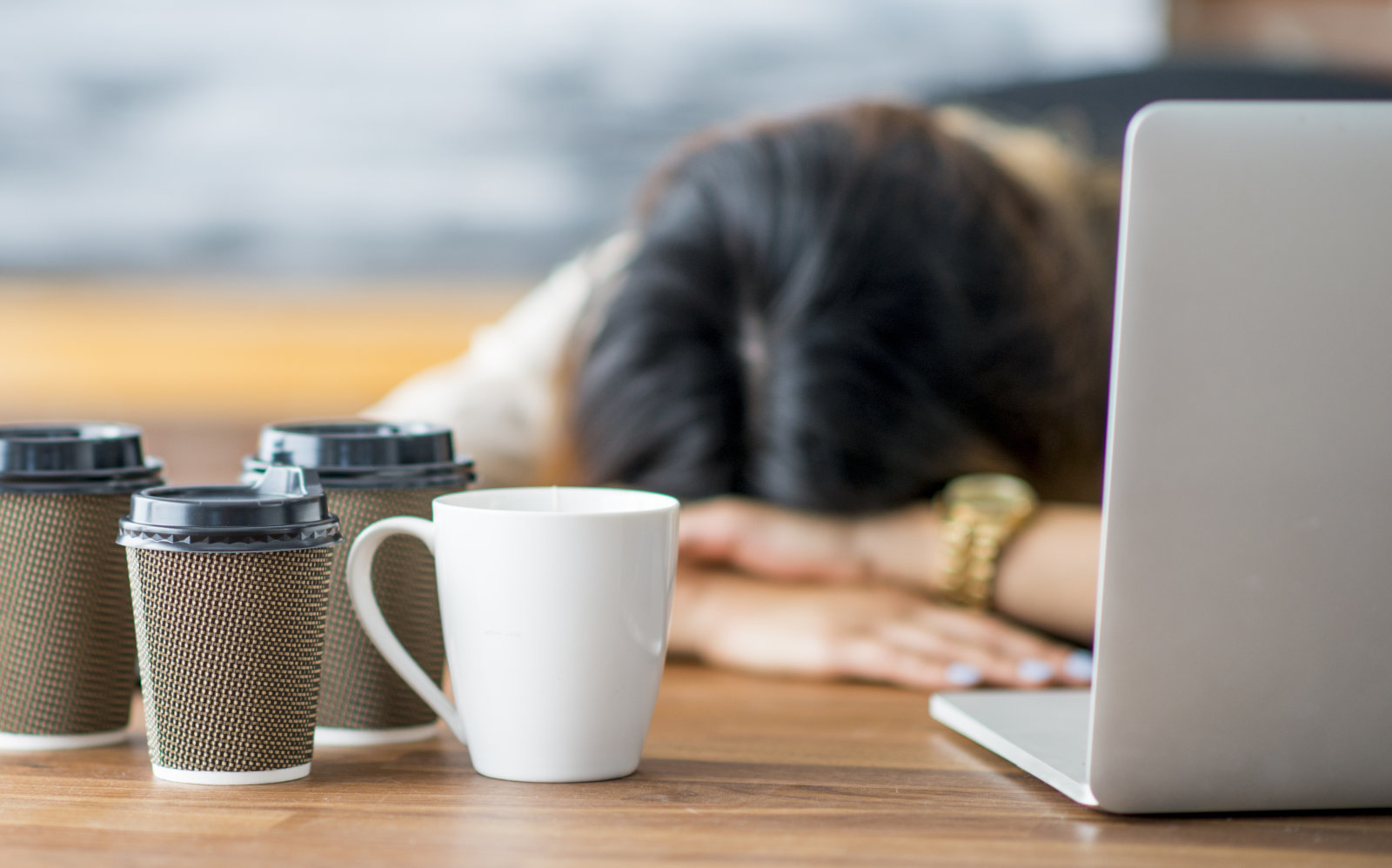 A female entrepreneur and businesswoman is working on her start up company in her office. She has fallen asleep at the office with her head on her desk. Empty coffee cups are on the table.