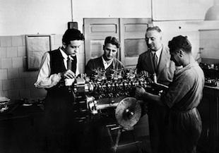 - Enzo Ferrari con il figlio Alfredo (Dino) ,a sinistra nella foto, osservano l'assemblaggio di un motore.