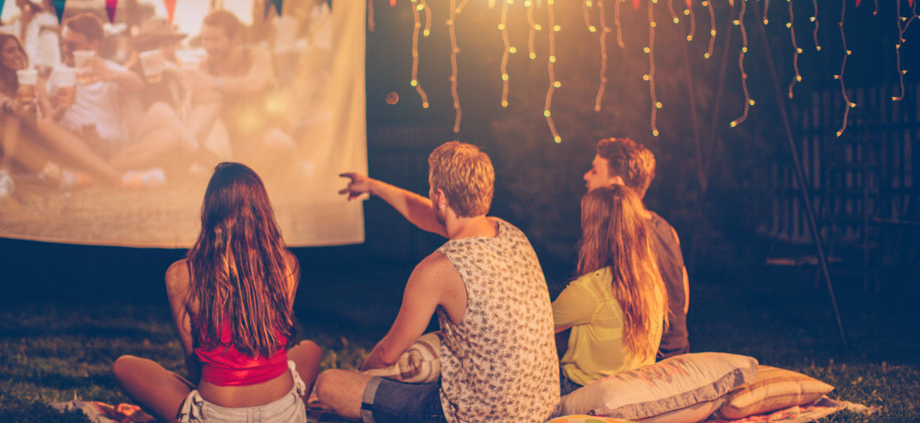 Young friends having movie night party. Laying down on blanket in front of movie improvised screen. Backyard decorated with festive string lights. Night time. View from behind.