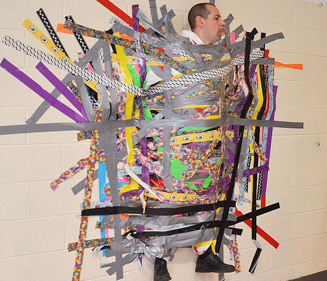 Teacher let's kids duct tape him to the wall