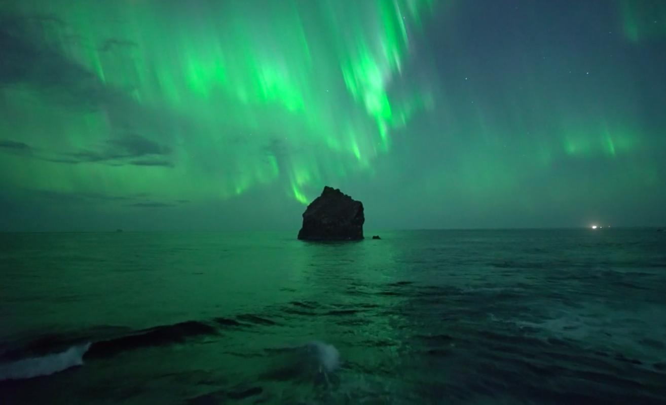 Polarlichter über einem Felsen im Meer bei Island