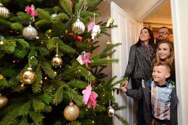 Penniston family given 25ft Christmas tree which bursts through the roof - one year after burglars stole their presents