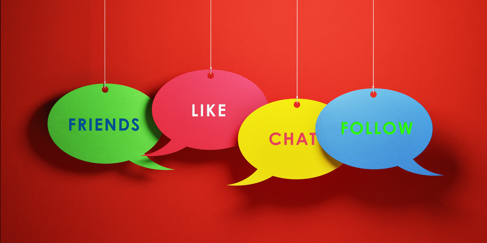 Green yellow red and blue colored chat bubbles over red background. Friends like chat follow writes on chat bubbles. Panoramic composition with copy space. Great use for social media concepts.