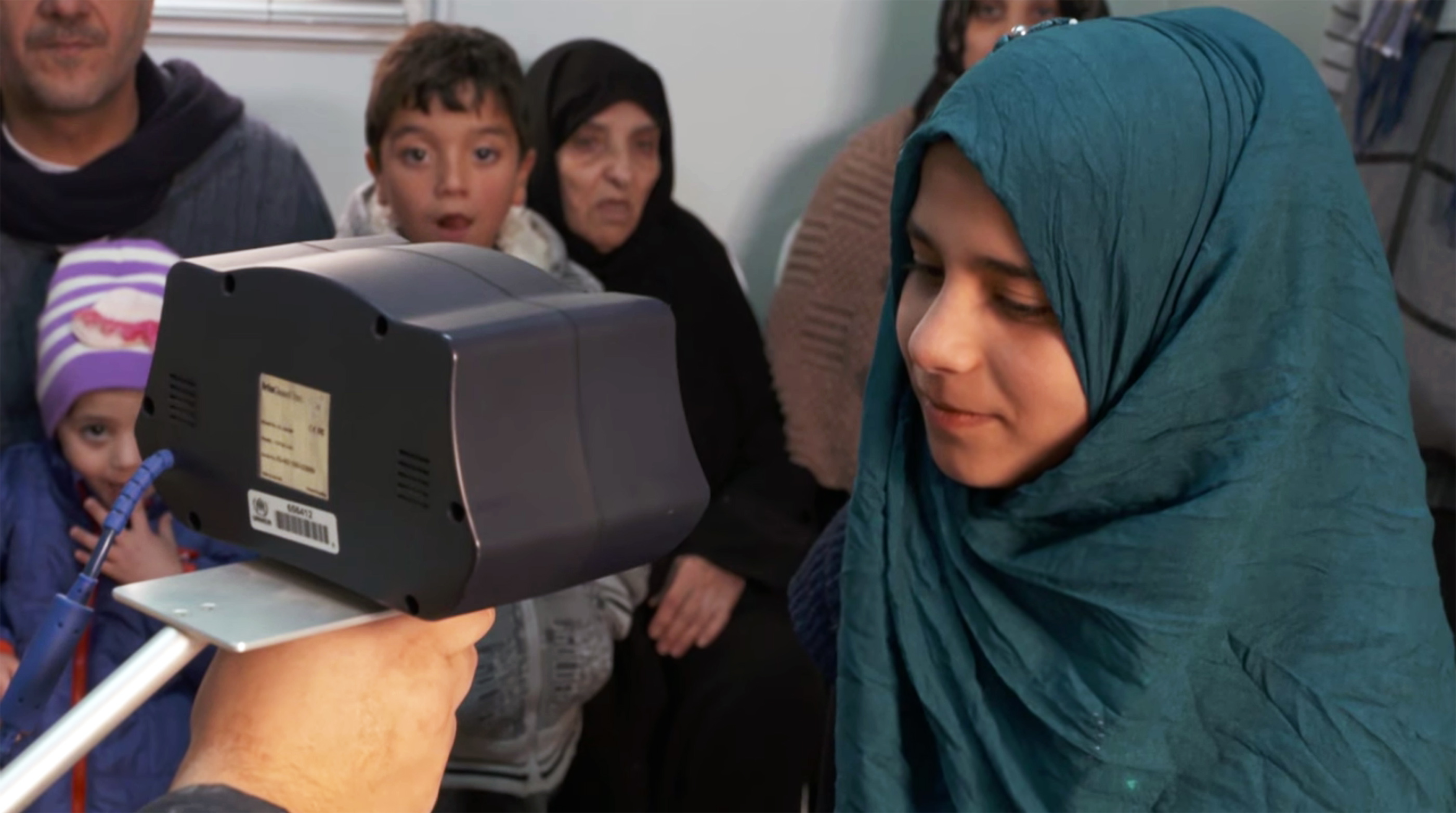 A UN worker scans the iris of a Syrian girl registering as a refugee at the Zaatari camp in Jordan.