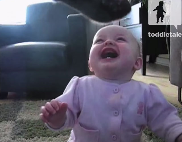baby laughs at dog eating popcorn