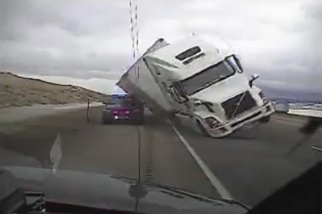 【ビデオ】強風に煽られた大型トレーラーが高速道路で横転 警察車両を押し潰す!