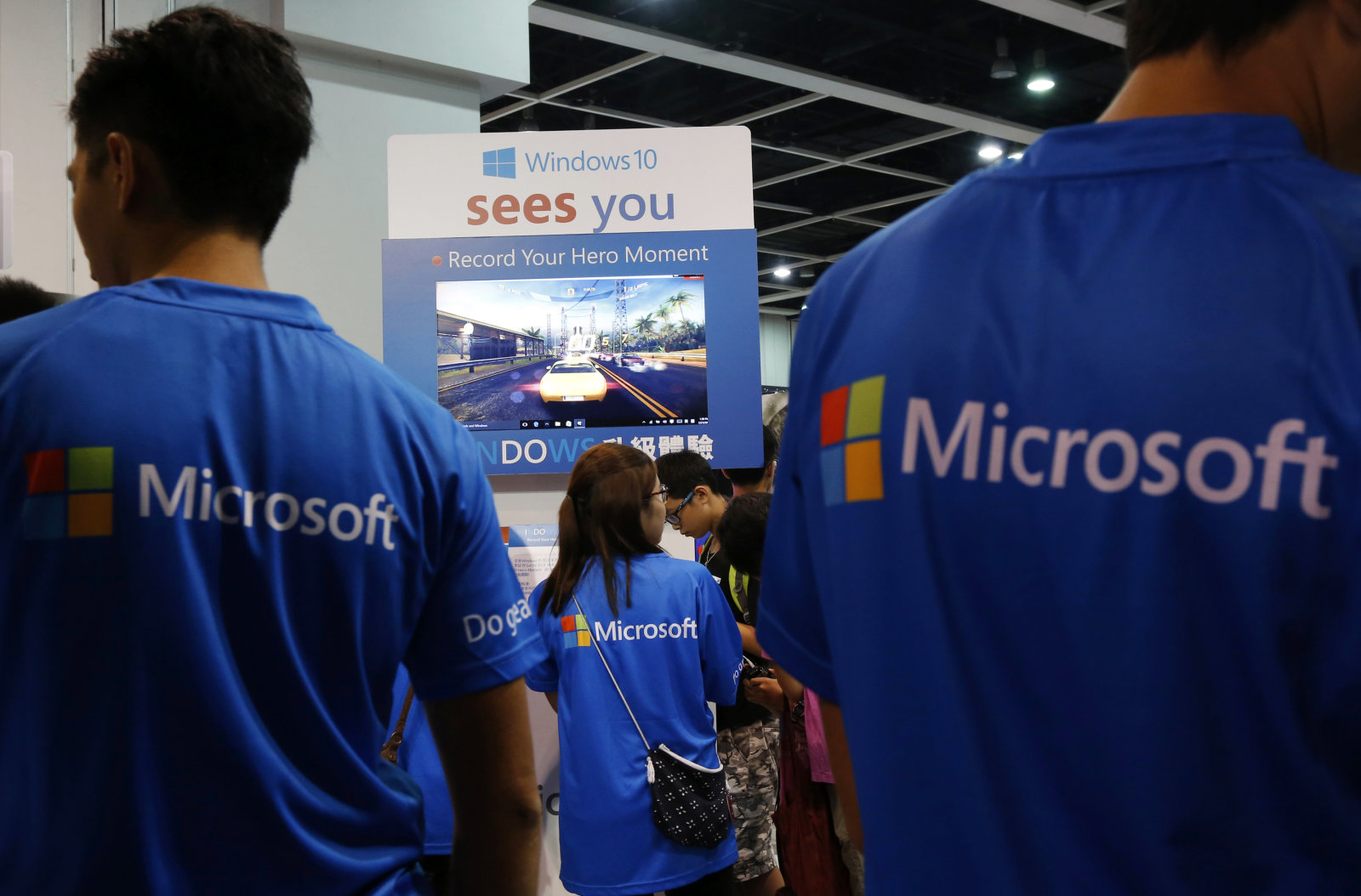 Promotional staff stand at the Microsoft Windows 10 booth two days before its global official launch at the Ani-Com & Games Hong Kong in Hong Kong, China, July 27, 2015. REUTERS/Bobby Yip