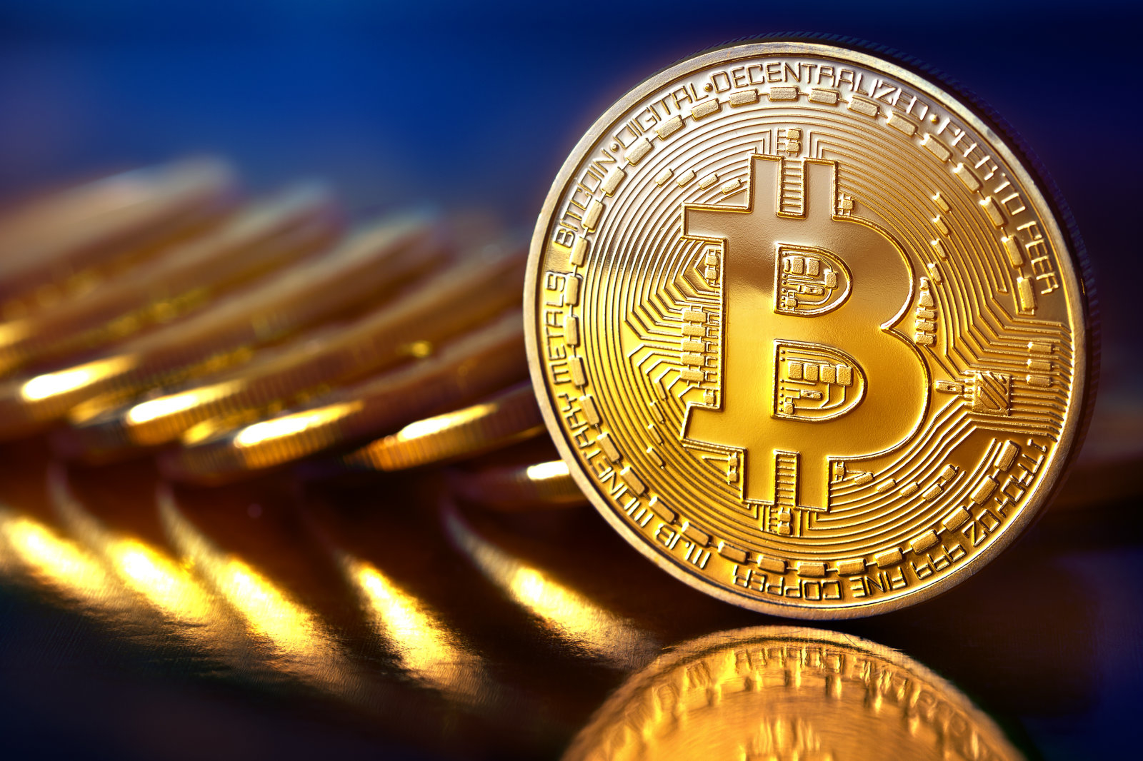 Prague, Czech Republic - January 1, 2000: Photo Golden Bitcoins (new virtual money ) Close-up on a blue background.