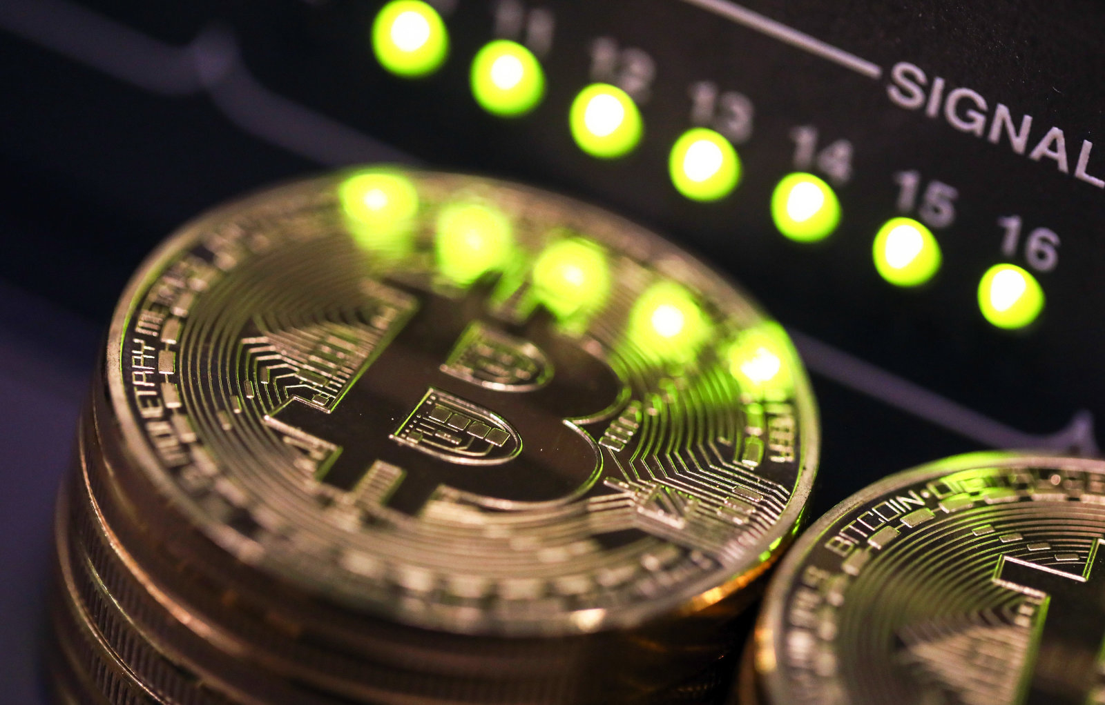 Stacks of bitcoins sit near green lights on a data cable terminal inside a communications room at an office in this arranged photograph in London, U.K., on Tuesday, Sept. 5, 2017. Bitcoin steadied after its biggest drop since June as investors and speculators reappraised the outlook for initial coin offerings. Photographer: Chris Ratcliffe/Bloomberg via Getty Images