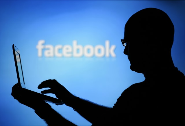 A man is silhouetted against a video screen with an Facebook logo as he poses with an Dell laptop in this photo illustration taken in the central Bosnian town of Zenica, August 14, 2013. REUTERS/Dado Ruvic (BOSNIA AND HERZEGOVINA - Tags: BUSINESS TELECOMS)
