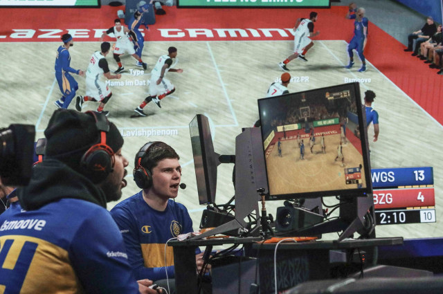 "A giant monitor shows play as Warriors Gaming Squad teammates Charles ""CB13"" Bostwick, center, from New York, and his teammate Alexander Reese, left, from Milwaukie, Or., react to scoring during the NBA 2k League (NBA2KL) professional esports playoffs, Wednesday, July 24, 2019, in Queens borough of New York. The teams kicked off day one of the NBA2KL playoffs with Blazers on the losing 67-45. (AP Photo/Bebeto Matthews)"