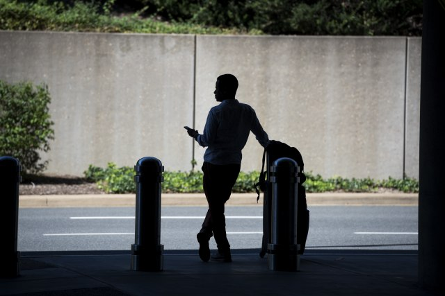 UNITED STATES - AUGUST 24: A man waits for a ride-hailing service at Ronald Reagan Washington National Airport, August 24, 2016. (Photo By Tom Williams/CQ Roll Call)