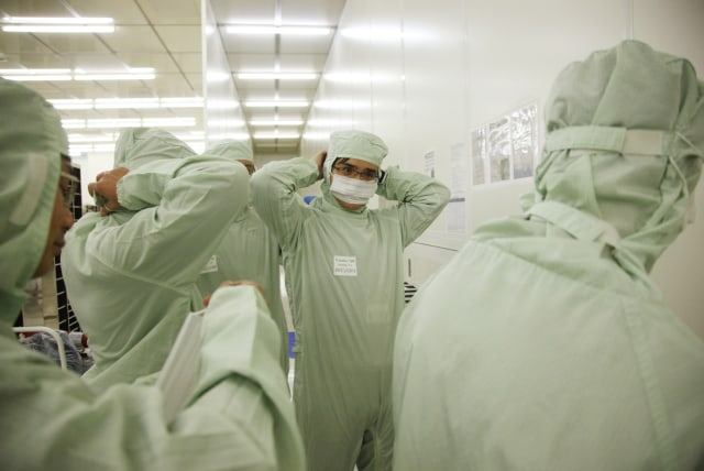 Employees put on clean suits before entering the wafer FAB of Semiconductor Manufacturing International Corp in Shanghai, China on 18 February, 2011.   The Taiwan based manufacturer is one of the largest chip foundries in the world. (Photo by In Pictures Ltd./Corbis via Getty Images)