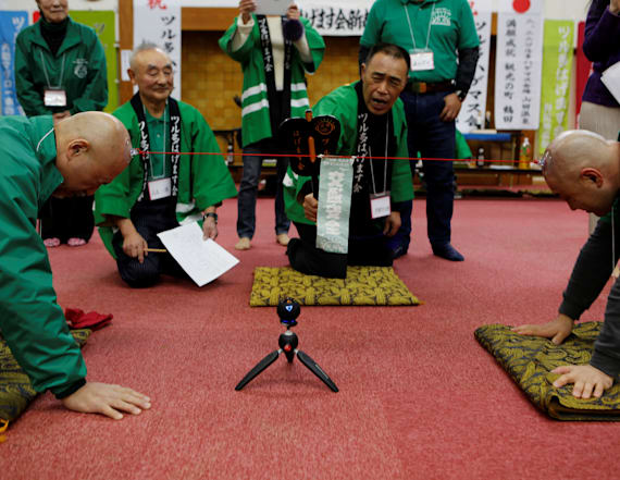 Bald men use their heads for tug-of-war competition