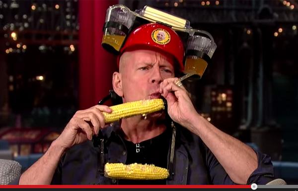 ブルース・ウィリスが手を使わずにトウモロコシを食べる装置を考案 トーク番組で自ら実演