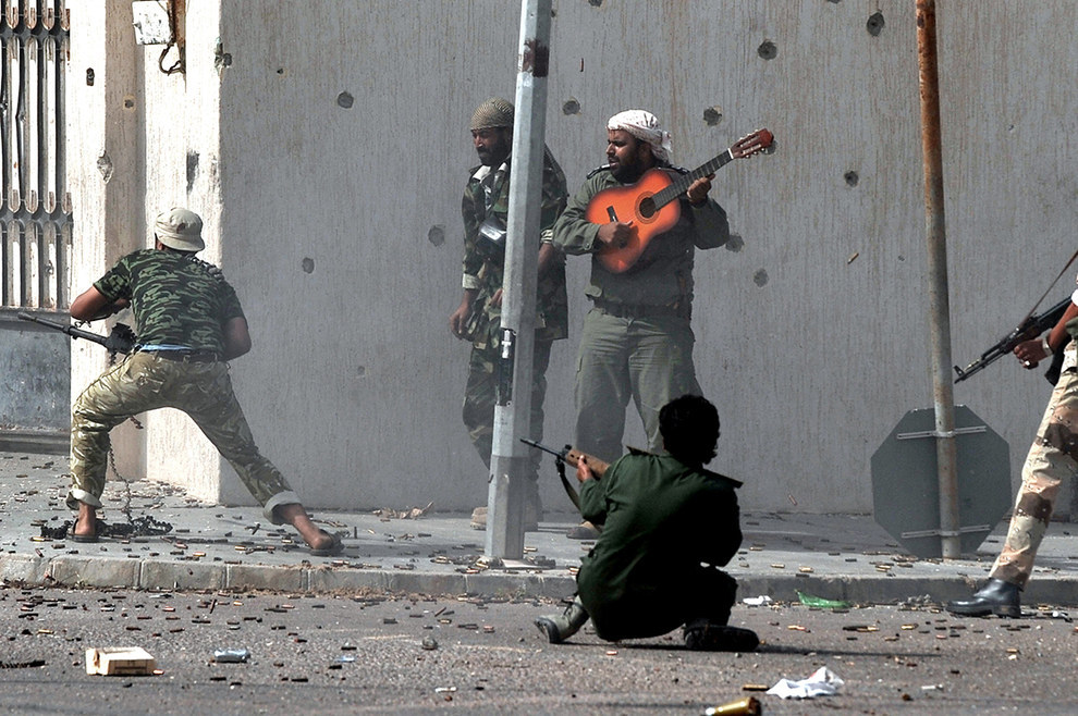 manliest photos on the internet, funny manly images, libyan man playing guitar in gunfight