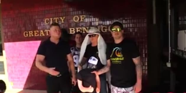 A still from the video, showing Cottrell (left) and other UPF members holding the dummy