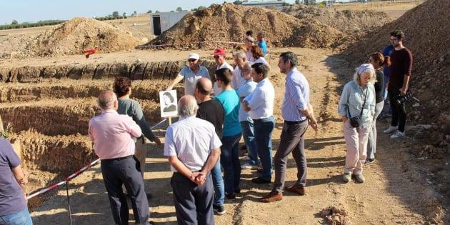 Un grupo de visitantes, ante la tierra abierta durante la excavación, en el cortijo de El Aguaucho.