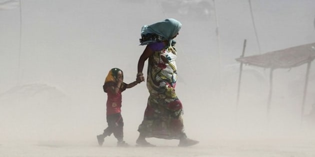 A mother and her child walk along the Ganges river during a dust storm on a hot summer day in Allahabad, India, June 9, 2015.