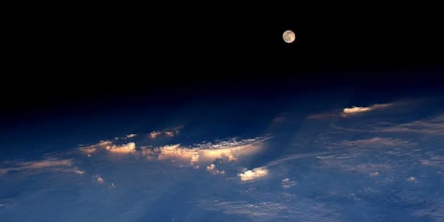 Astronaut Jeff Williams took this photograph of the rare Strawberry Moon emerging from the clouds while orbiting Earth from the International Space Station on Tuesday.