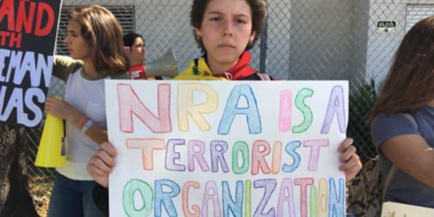 「NRAはテロリストの組織だ」というプラカードをかかげる抗議デモ参加者