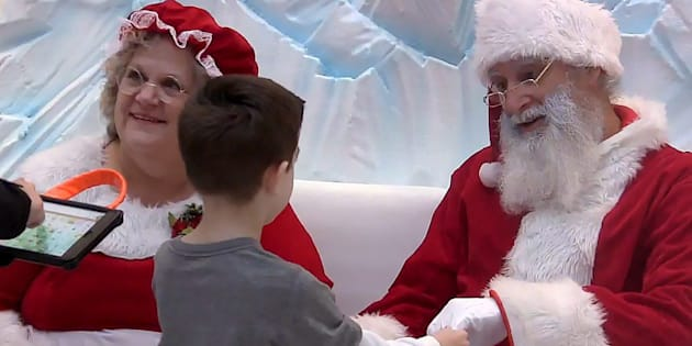 "Tyson Lehr meets Santa, Robert Blais, and Mrs. Claus, Cheryl Agostino, while his mother Bethany Lehr looks on during a special ""Silent Santa"" session for children with autism at Londonderry Mall, in Edmonton, in this still image made from video on Dec. 17."
