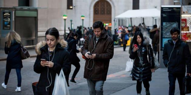 Tres peatones caminan mirando sus teléfonos móviles en Wall Street, Nueva York.