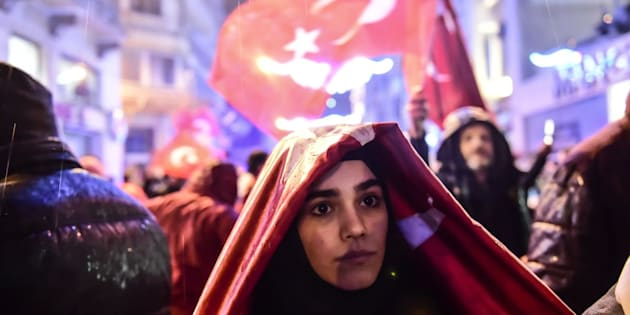 A woman covers herself from rain with the Turkish national flag during a demonstration on March 12, 2017 in front of the Netherlands consulate in Istanbul.  The Dutch embassy in Ankara and consulate in Istanbul have been sealed off for 'security reasons', Turkish foreign ministry sources said on Saturday, as tensions soar between Turkey and the Netherlands. / AFP PHOTO / YASIN AKGUL        (Photo credit should read YASIN AKGUL/AFP/Getty Images)