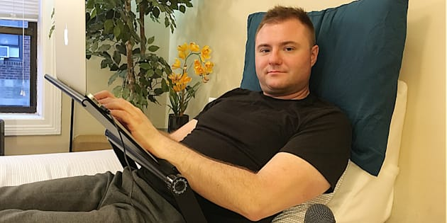 Rick Lunkenheimer tumbado en un ángulo de 45 grados sobre una almohada cuña, con más cojines para apoyar el cuello, con un escritorio ajustable y con un micrófono de reconocimiento de voz.