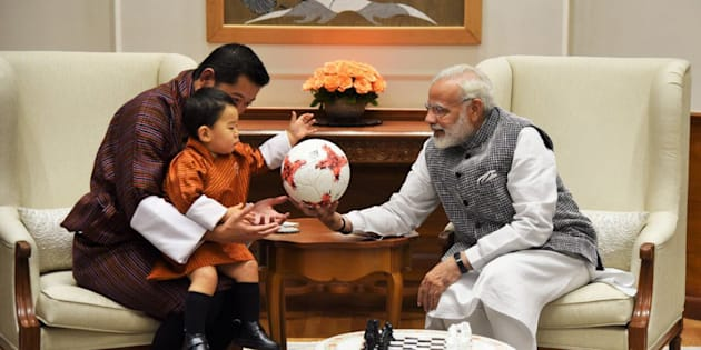 Modi presents the Prince of Bhutan with an official football from the FIFA U-17 World Cup.