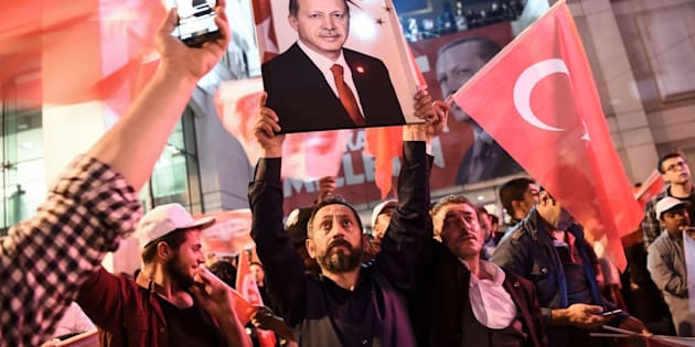 A supporter of the 'yes' brandishes a picture of Turkish president Recep Tayyip Erdogan among other supporters waving Turkish national flags during a rally on Sunday