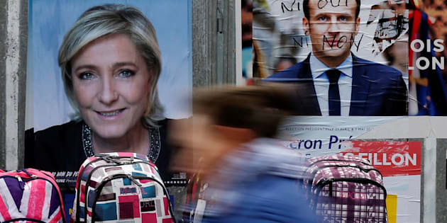 A woman walks past official posters of candidates for the 2017 French presidential election Marine Le Pen, French National Front (FN) political party leader (L) and Emmanuel Macron, head of the political movement En Marche !, or Onwards !, (R) on a local market in Bethune, France April 24, 2017.  REUTERS/Pascal Rossignol