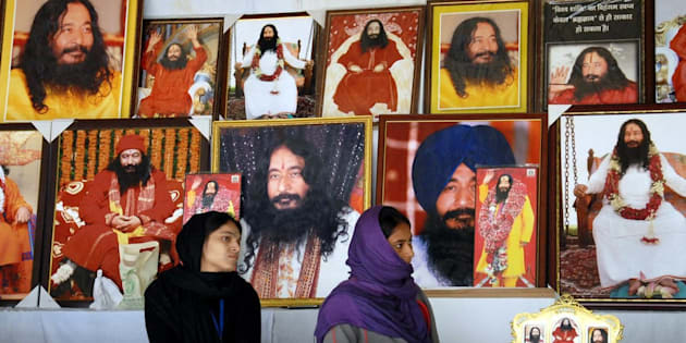 Indian followers of deceased guru Ashutosh Maharaj Divya Jyoti Jagriti Sansthaan sit front posters bearing his image at a stall during a congregation at his ashram ahead of a High Court hearing to discuss his possible cremation in Nurmahal some 30kms from Jalandhar on December 14, 2014. Ashustosh Maharaj was declared clinically dead on January 2014 but his body has been kept in a deep-freeze at his ashram with followers confident he will return to life to lead them. AFP PHOTO / STR        (Photo credit should read STR/AFP/Getty Images)