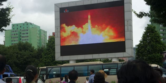 People watch as coverage of an ICBM missile test is displayed on a screen in Pyongyang on Saturday.