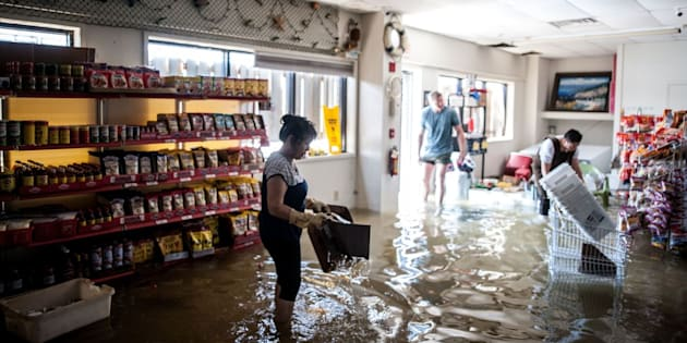 Hanh Nguyen, owner of Marie's Seafood Market, attempts to salvage goods from her store with the help of her family.