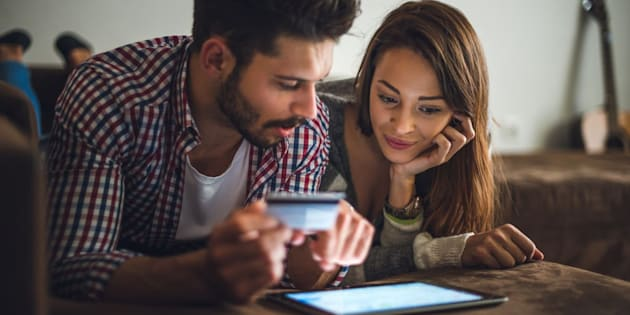 Man holding a credit card and shopping online with his girlfriend.