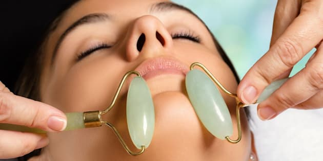Macro close up portrait of woman having facial beauty treatment in spa. Therapist massaging chin with jade rollers.