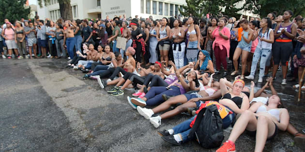 Rhodes University students lie on their backs during protests against sexual violence in the institution on April 19, 2016, in Grahamstown, South Africa. This, after the names of 11 students accused of rape were posted on social media.