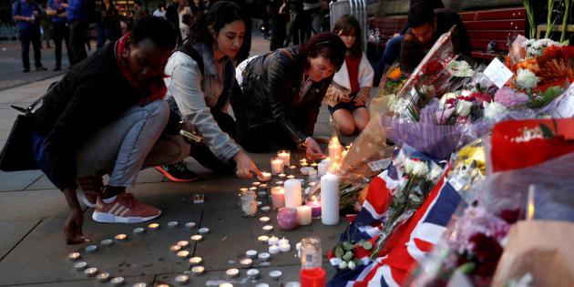 Un grupo de mujeres coloca velas y flores en el memorial por las víctimas, en el centro de Manchester, el pasado mayo.