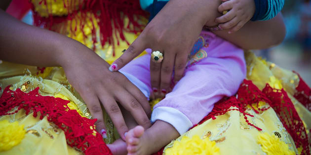 Shanya*, 15 anos, segura a filhinha de 5 meses que já está prometida para se casar com um garoto da vizinhança quando atingir 13 anos.