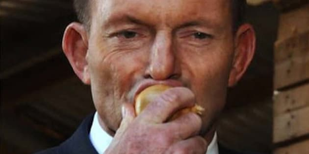 "Tony Abbott eats a ""normal sized"" raw onion during a visit to Tasmania in 2015."