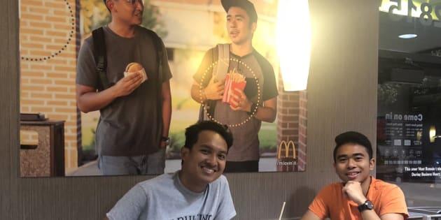 Jevh et son ami Christian, devant le faux poster d'eux-mêmes collé dans un restaurant McDonald's.