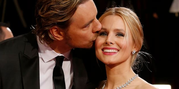 Actress Kristen Bell gets a kiss from her husband, actor Dax Shepard at the 86th Academy Awards in Hollywood, California March 2, 2014. REUTERS/Adrees Latif (UNITED STATES  - Tags: ENTERTAINMENT)(OSCARS-ARRIVALS)