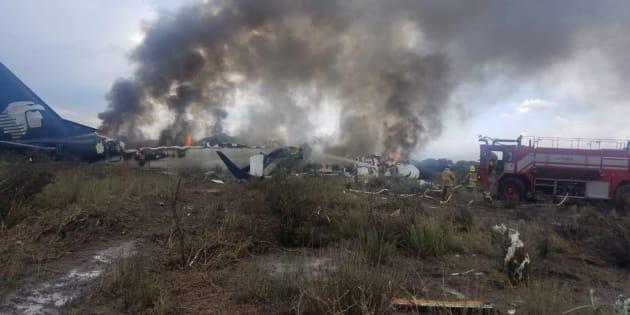Los bomberos disparan un incendio mientras el humo se eleva sobre el sitio donde se estrelló un avión de pasajeros Embraer operado por Aeroméxico en el estado mexicano de Durango.
