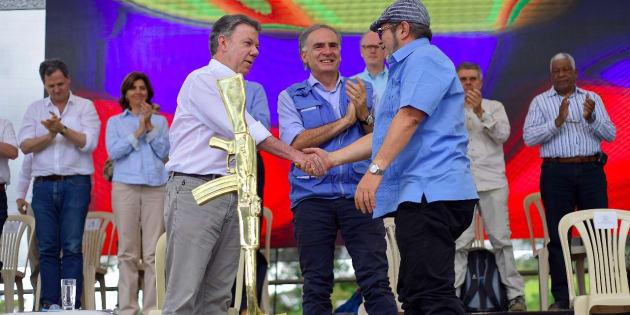 O presidente colombiano Juan Manuel Santos e o líder das Farc Rodrigo Londono celebram o histórico acordo de paz.