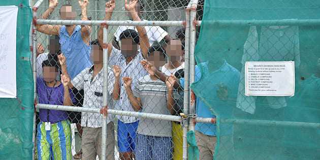 Asylum-seekers look through a fence at the Manus Island detention centre in Papua New Guinea March 21, 2014. Eoin Blackwell/AAP/via Reuters
