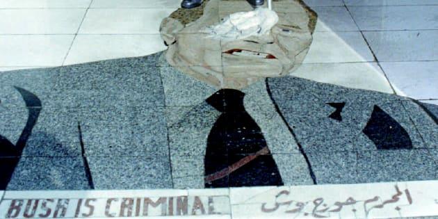 Un employé nettoie la mosaïque à l'image de George H. W. Bush à l'entrée de l'hôtel al-Rachid