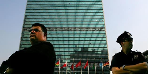 Personal de vigilancia y policías, atentos a lo que ocurría entre los funcionarios evacuados del edificio de la ONU, a sus espaldas.