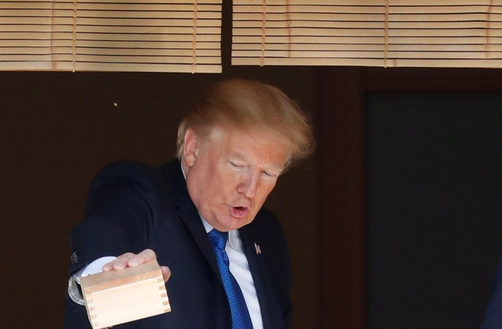 Photo of donald trump dumping fish food into koi pond for Trump feeding fish