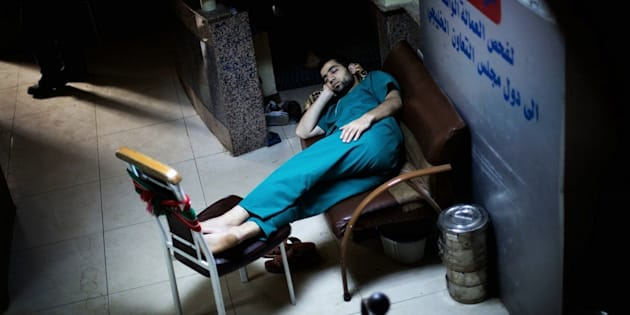 A Syrian doctor sleeps in the waiting room of Dar al-Shifa hospital in Aleppo on Oct. 21, 2012.
